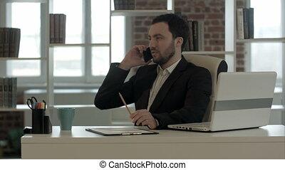 Man talking on mobile phone while using laptop computer
