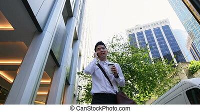 Man talking on mobile phone while walking on street 4k - Low...
