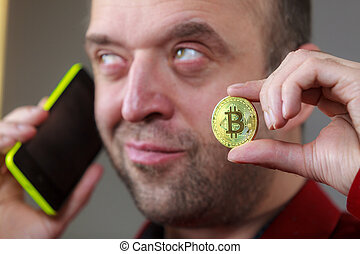 Man talking on phone holding bitcoin
