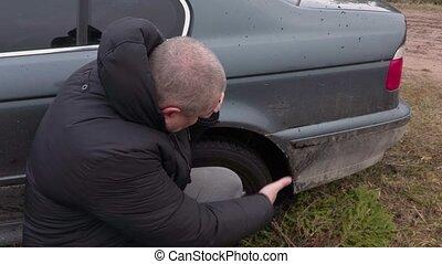 Man talking on phone near stuck car in the mud