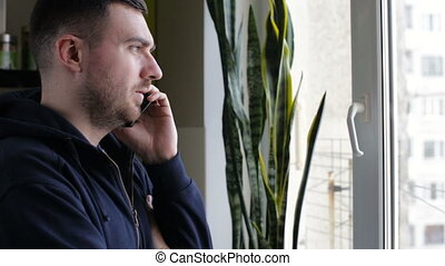 Man talking on phone standing by window at home