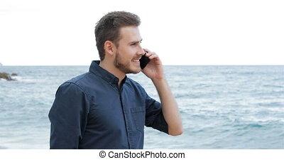 Man talking on phone walking on the beach - Happy man...