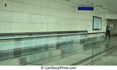 Man talking on phone walking through airport