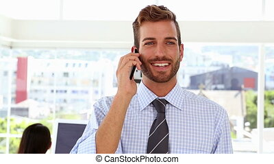 Man talking on phone while colleag