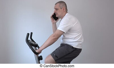 Man talking on smart phone and using exercise bike