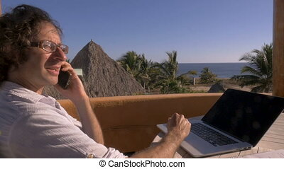 Man talking on smart phone while working in home office at...