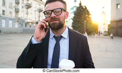 Man talking on smartphone and drinking coffee walking down the street. Slow motion