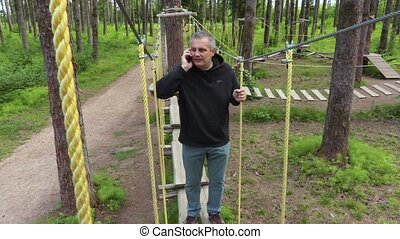 Man talking on smartphone on aerial obstacle course