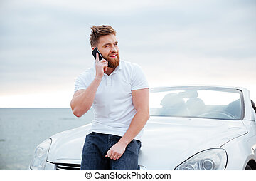 Man talking on the mobile phone while leaning at car