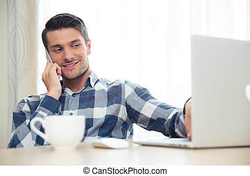 Man talking on the phone and using laptop at home