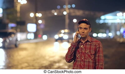 man speaks on the phone near the road at night