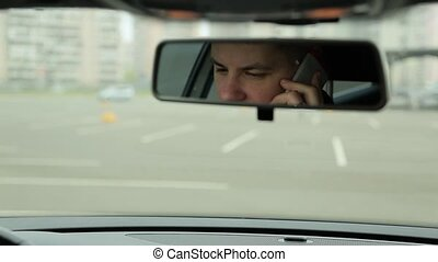 Man talking on the phone in the car mirror view