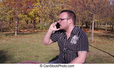 Man talking on the phone on a bench in park