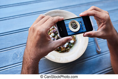 Man talking pictures of his salad at a bistro table - Man...