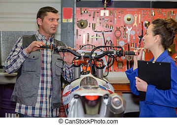 man talking to assistant and fixing a motorcycle