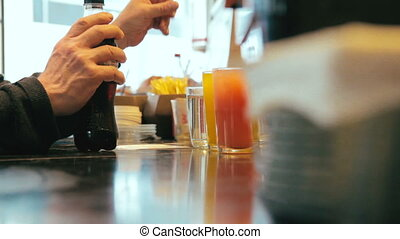 Man talking to bartender while taking a cola bottle from the at cafe