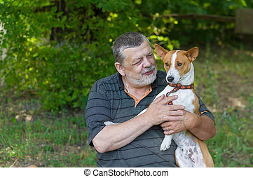 Man talking to his cute basenji dog he taking it in the hands