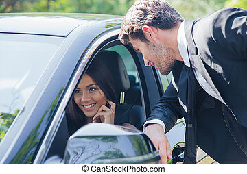 Man talking with woman in car