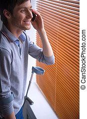 Man talks by phone near window with broken leg
