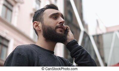 Man talks on his Smartphone walking around the city