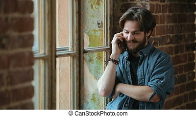 Man Talks on Phone by Window - Handsome caucasian man...