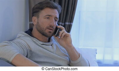 Man talks on the phone at home