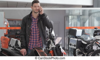 Man talks on the phone near motorbike