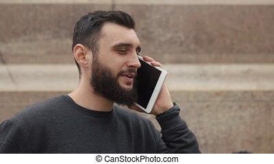 Man talks on the tablet sitting on the footsteps