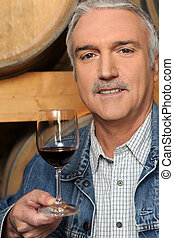Man tasting a glass of red wine in a vineyard