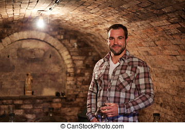 Man tasting a glass of white wine in wine cellar.