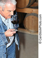 man tasting wine in storehouse