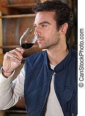 Man tasting wine in winery