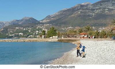Man teach little child to throw stones into water in very picturesque place.