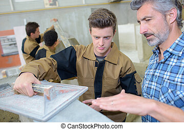 Man teaching apprentice to float cement