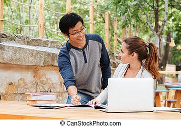 Man teaching pretty young woman outdoors