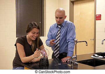 Man teaching science to a female student.
