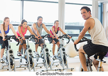 Man teaching spinning class to four people - Portrait of a ...