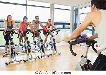 Man teaching spinning class to four people - Cropped man...