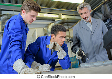 Man teaching students to weld