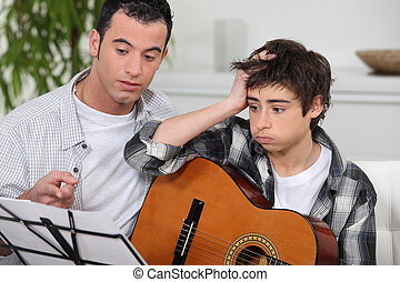 Man teaching to boy how to play guitar