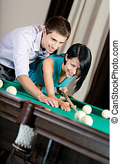 Man teaching woman to play billiards