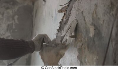 man tears off pieces from an old wall.
