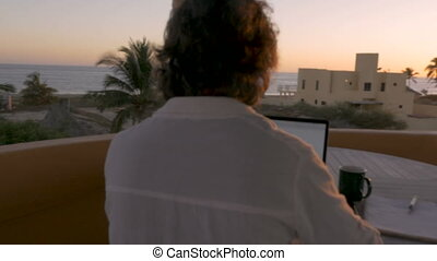 Man telecommuting on computer during sunrise or sunset with...