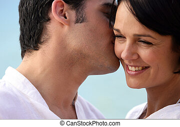 Man tenderly kissing woman