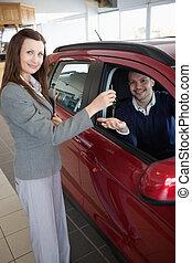 Man tending his hand while receiving car keys
