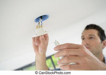 man, ter vervanging, schijnwerper, in, plafond