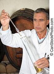 Man testing brandy in a cellar