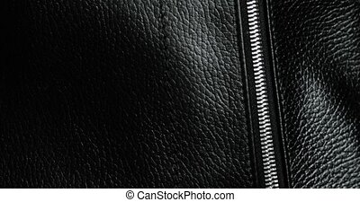 Man tests zips and unzips metal zipper on leather black bag, hand closeup view. Macro shot of unzipping and zipping metallic zipper on black leather accessory with guy's hand. Expensive brutal accessory.