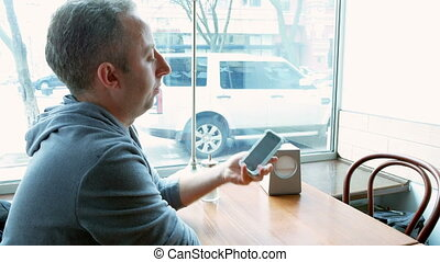 Man texting and browsing with mobile app in a cafe