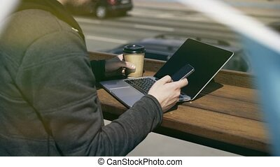 Man texting and drinking coffee to go while working outdoors
